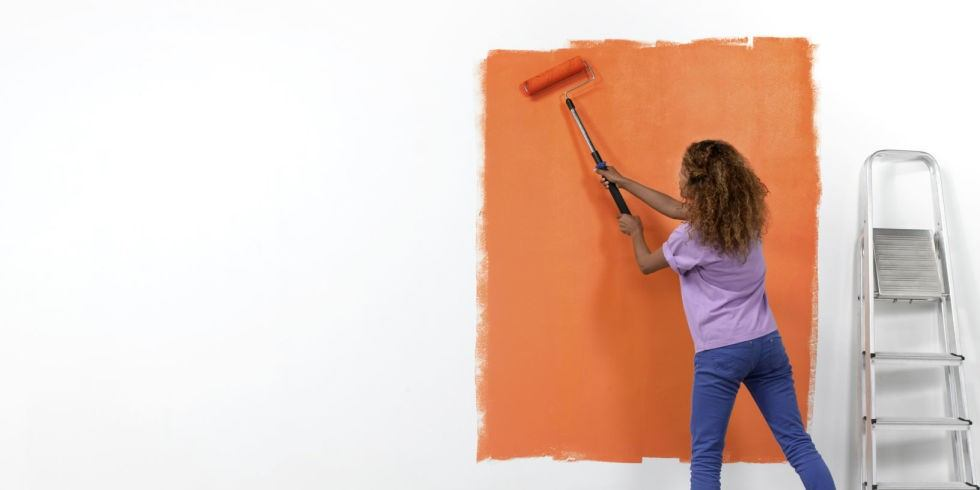 Kid painting the orange wall