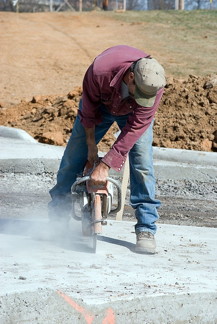 Man using power tool to cut cement