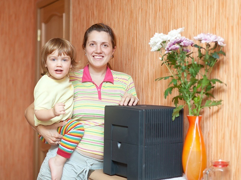Woman and child uses humidifier at home